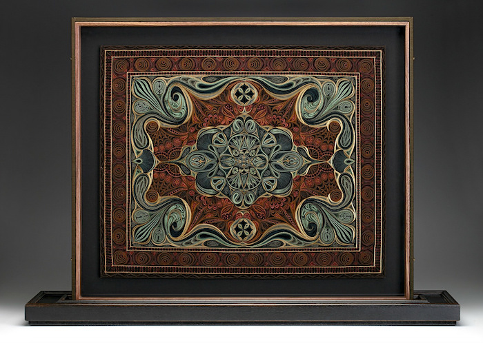 ein bild mit einem teppich mit vielen kleinen quilling figuren aus roten, grünen und braunen quilling papierstreifen, basteln für erwachsene
