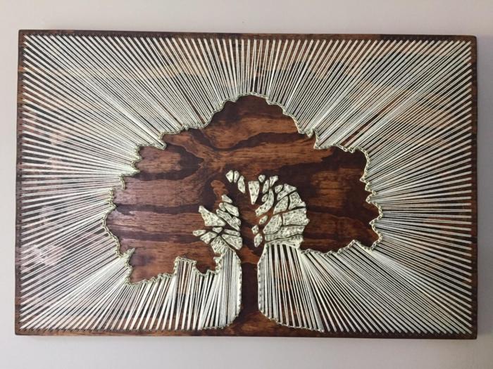 ein Baum mit prächtiger Krone im Sommer, Schattenbild mit weißen Faden umgeben, Fadenbilder
