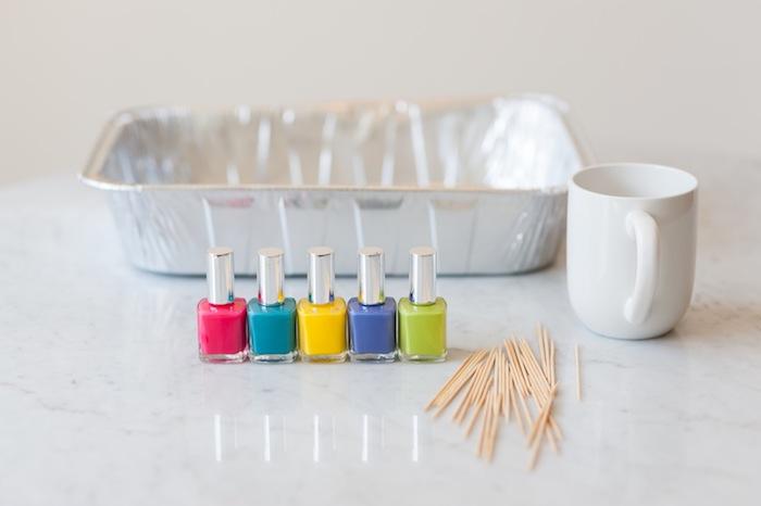 Bunte Tassen selbst gestalten, dazu brauchen Sie verschiedene Nagelläcke, weiße Tassen, eine Schale mit lauwarmem Wasser und Holzstäbchen
