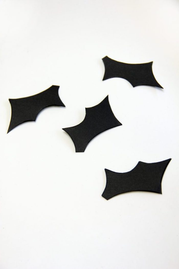 vier kleine schwarze selbstgebastelte fledermaus flügel aus papier und ein weißer tisch, eine fledermaus aus papier selber basteln