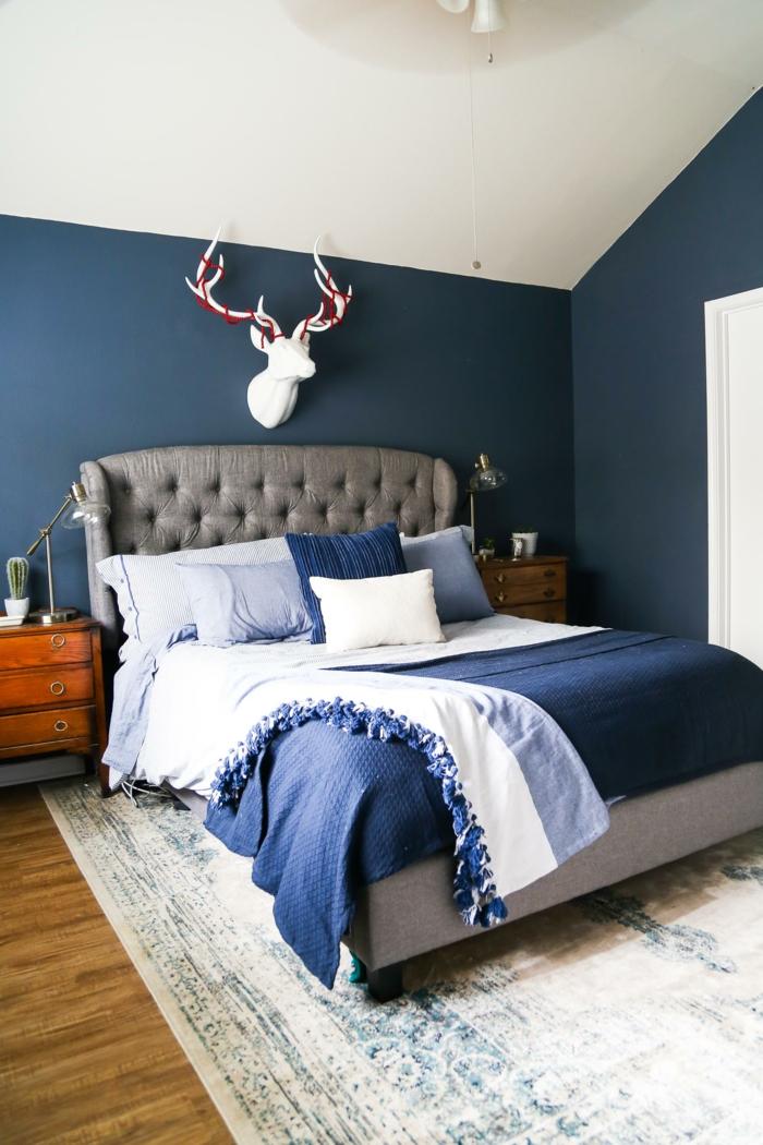 eine Dachgeschoss Wohnung, ein graues Bett, blaues Bettbezug, veralteter Perserteppich