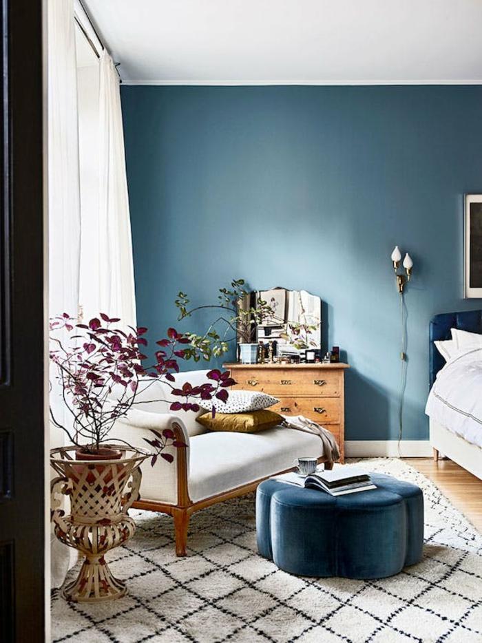 eine Leseecke im Schlafzimmer modern gestalten, weißer, bequmer Sessel, ein blauer Hocker
