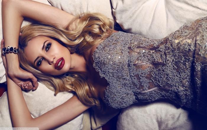 Lange blonde Haare, knallroter Lippenstift und Smokey Eyes, graues Spitzenkleid, armband mit schwarzen Steinen