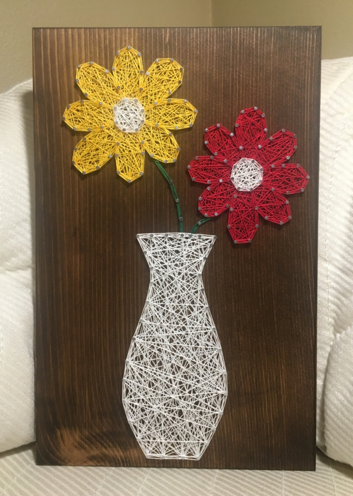 Zimmerdeko mit Fadenbilder Blumen in gelber und in roter Farbe in einer weißen Vase