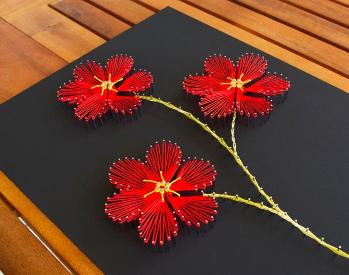 drei Blumen in roter Farbe, Blumen Fadenbilder auf einem schwarz gestrichenen brett