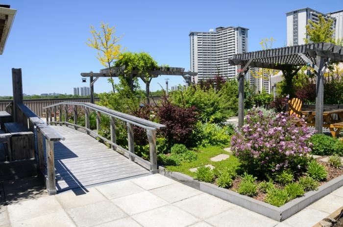 zwei Pergolen, eine Brücke, lila Blumen, eine originelle Terrassenbepflanzung