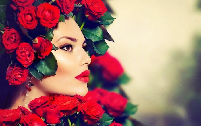 Schöne Frau mit braunen Augen, Porzellanteint und knallroten Lippen, viele rote Rosen