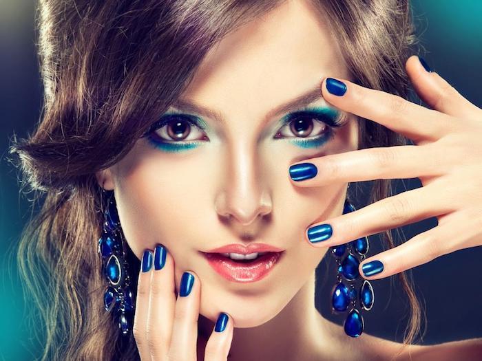 Braune Augen mit braunem Lidschatten schminken, dunkelblauer Nagellack und Ohrringe mit blauen Steinchen