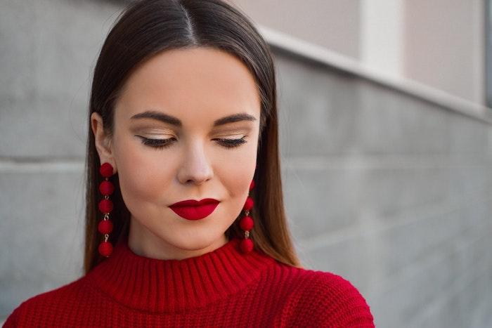 Schminke für braune Augen, goldener Lidschatten und Lidstrich, knallroter Lippenstift, Ohrringe mit roten Steinchen, roter Pullover, glatte lange Haare
