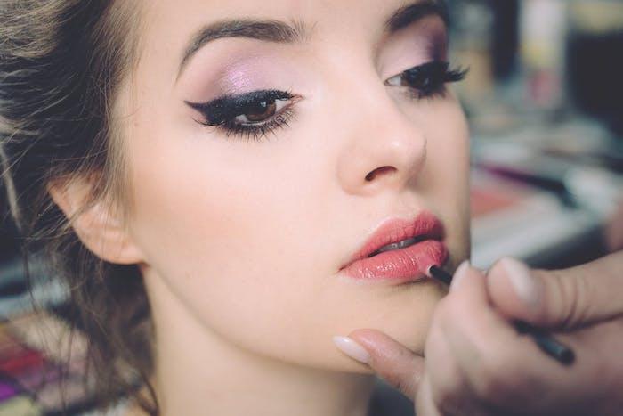 Lippenstift auftragen, lila Lidschatten und Lidschatten, kastanienbraune Haare und Porzellanteint