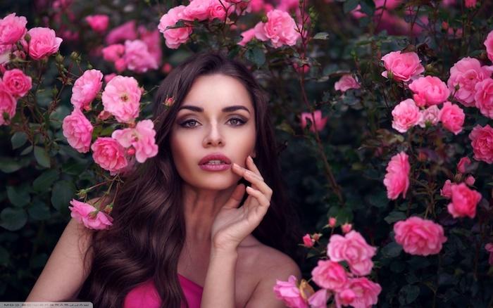 Smokey Eyes und matter Lippenstift, lange schwarze Haare mit schönen Wellen, viele rosafarbene Rosen