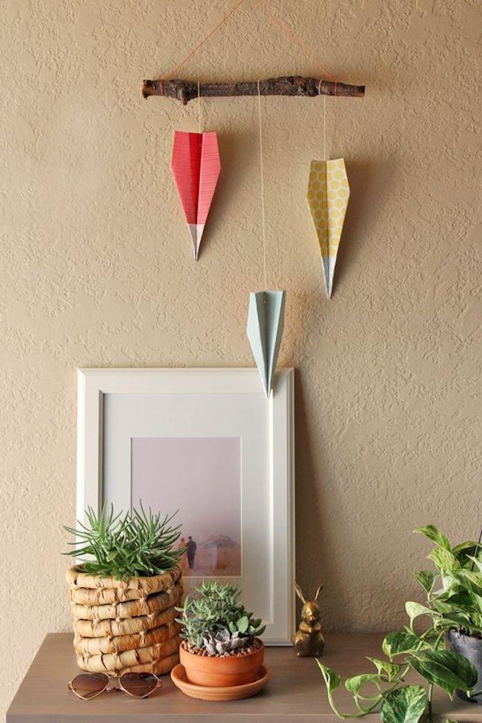 ein tisch aus holz, brille und blumentöpfe mit grünen pflanzen, rote, blaue und gelbe papierflieger, dekoration mit papierfliegern