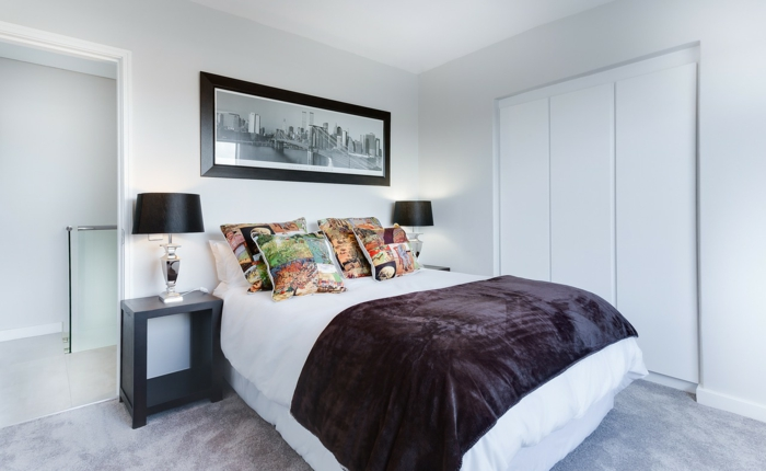 eingebauter weißer Schrank, ein großes Doppelbett mit bemusterten Kissen, Schlafzimmer modern einrichten