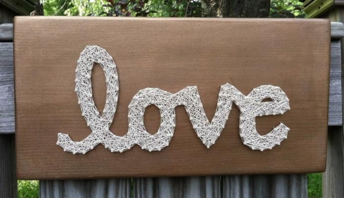 das Wort Liebe auf Englisch an einer Tabelle geschrieben, String Art Vorlage