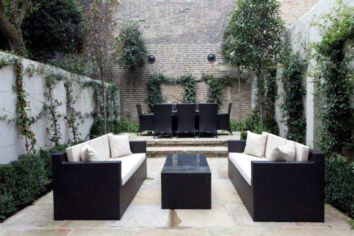 zwei Sofas, Stühle aus Rattan in Hintergrund, eine Backstein Wand, grüne Terrassenbepflanzung