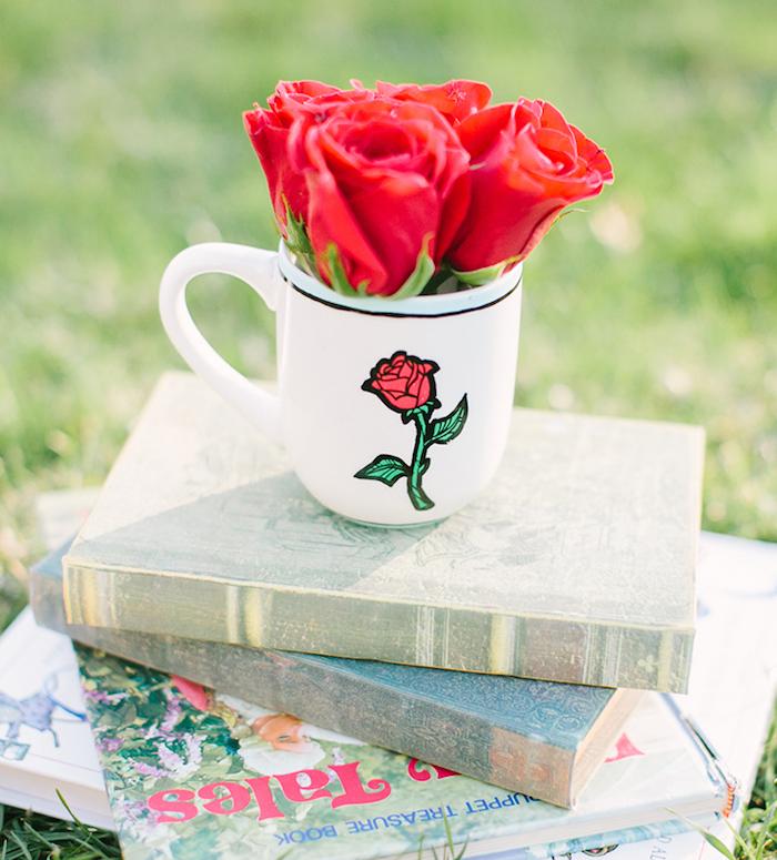 """Weiße Tasse mit der Rose aus """"Die Schöne und das Biest"""", kleiner Rosenstrauß und einige Bücher"""