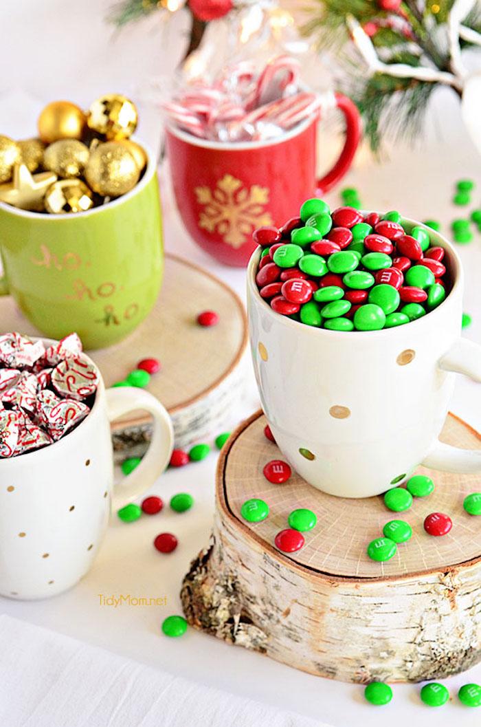 Schöne Geschenkidee zu Weihnachten, selbst bemalte Tassen voll mit Bonbons, Zuckerstangen und Weihnachtskugeln