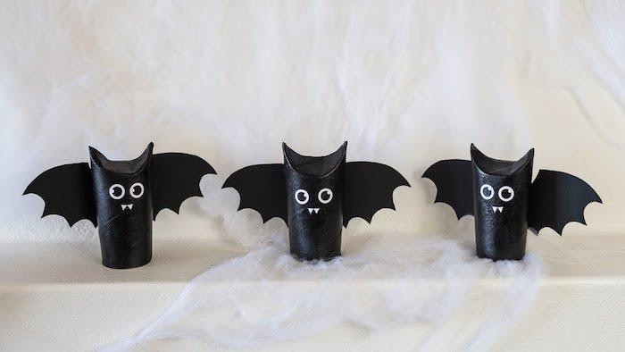 dekoration mit drei kleinen schwarzen fledermäusen mit schwarzen augen, weißen zähnen und schwarzen flügeln aus papier, fledermaus basteln aus klorollen