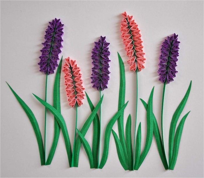 ein bild mit drei violetrten quilling blumen , frühling basteln, zwei pinke blumen aus papierstreifen und mit grünen blättern aus papier