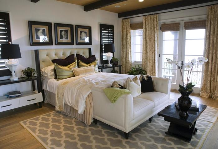 ein Boxspringbett, gepolstert, ein Teppich mit Mustern, drei Bilder, Schlafzimmer modern gestalten