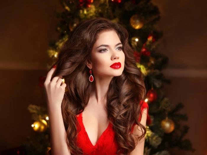 eine schöne frau mit rotem kleid, roten ohrringen, große braune haare, lockig, lippenstift rot