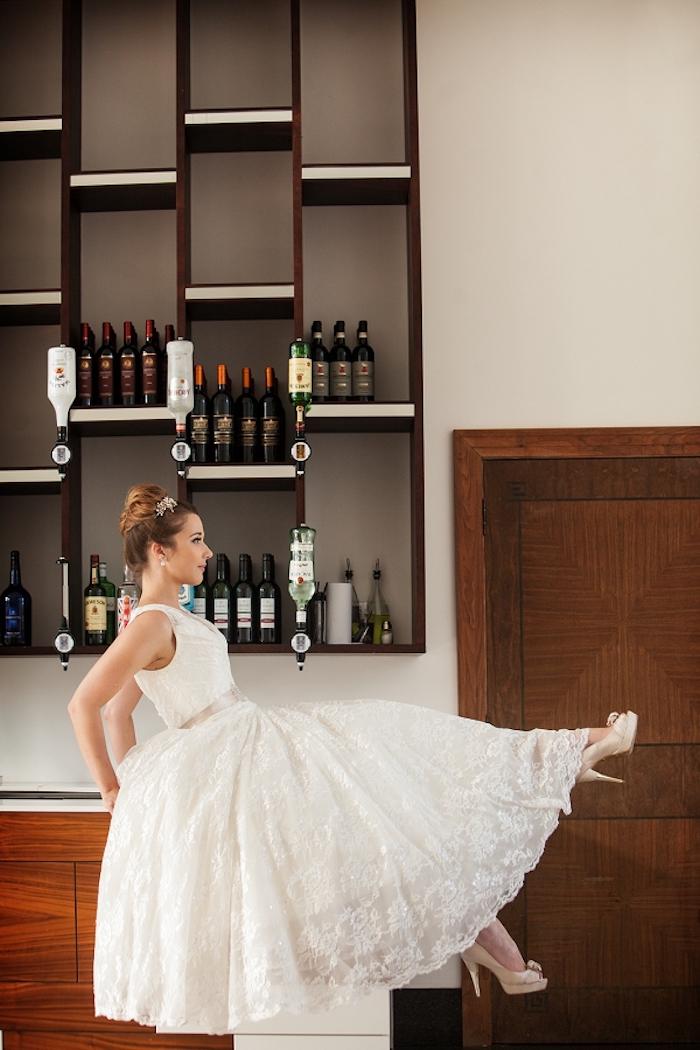 Brautkleid mit Spitzenelementen, locker fallend, High Heels in Beige, elegante Dutt Frisur mit silbernem Haarschmuck