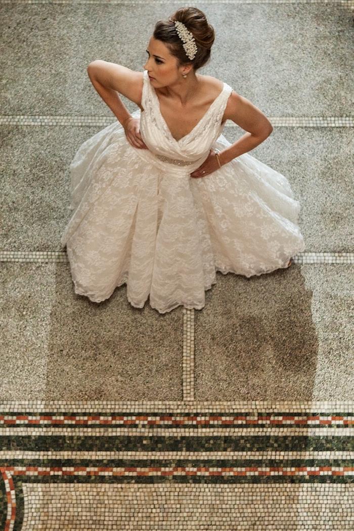 Dutt Frisur mit silbernem Haarschmuck, bodenlanges Brautkleid mit Spitzenelementen