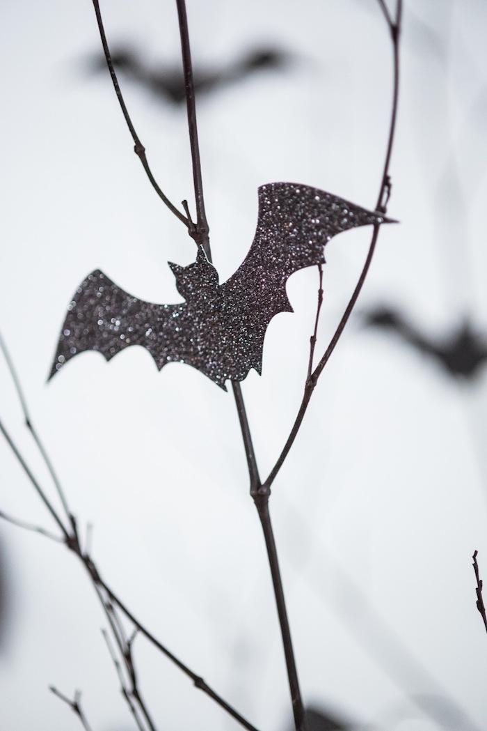 eine kleine fliegende schwarze fledermaus aus papier selber basteln, ein baum mit ästen, eine fledermaus mit schwarzen flügeln und kleinen schwarzen ohren