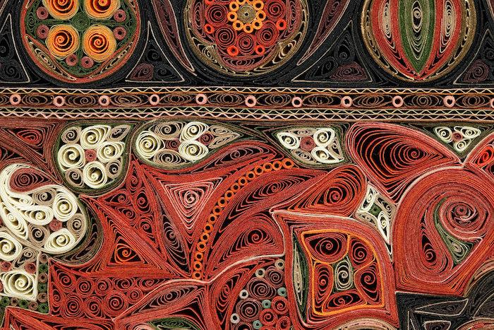 ein quilling bild mit vielen kleinen quilling elementen aus weißen, schwarzen, roten, braunen, gelben und grünen langen papierstreifen, quilling basteln mit papierstreifen