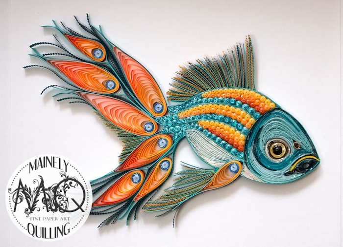 ein grüner quilling fisch mit schwarzen augen und mit einem großen orangen schwanz aus langen quilling papierstreifen, basteln mit kindern