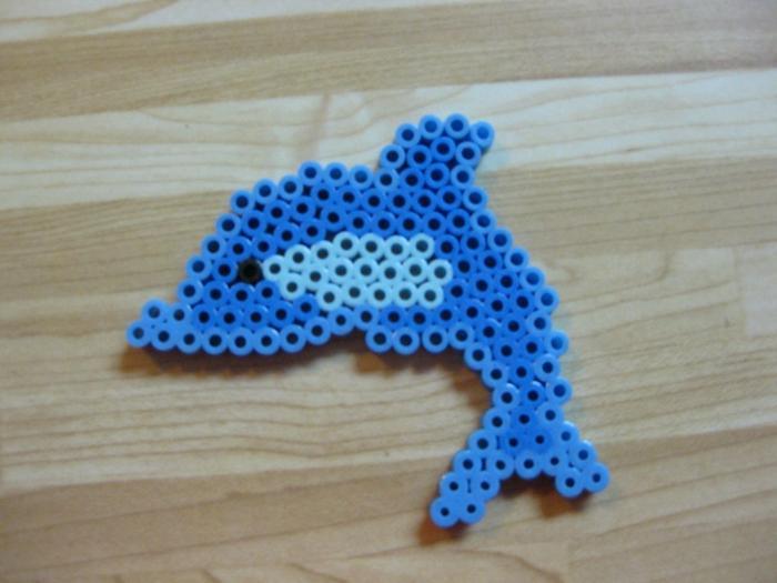 kleine Figur aus Steckperlen, ein winziges blaues Delfin mit schwarzen Perlenauge