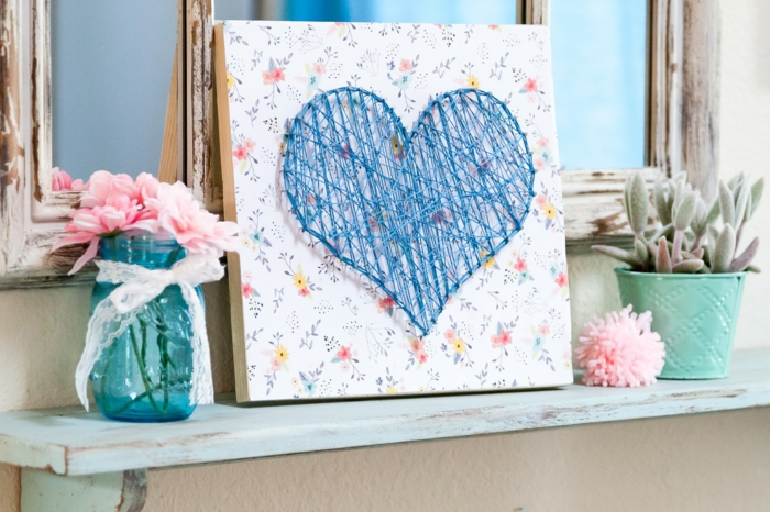 Nagelbilder mit blauen Fäden, Herzform an einerschönen Tafel mit Blumenmuster versehen