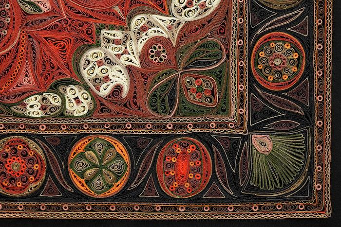 ein quilling bild mit einem teppich, bastelideen für erwachsene, ei n teppich aus grünen, roten, schwarzen, weißen, braunen und orangen papierstreifen