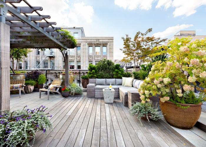 moderne Terrasse mit Bretten Bodenbelag, große Ziersträuche als Dekoration