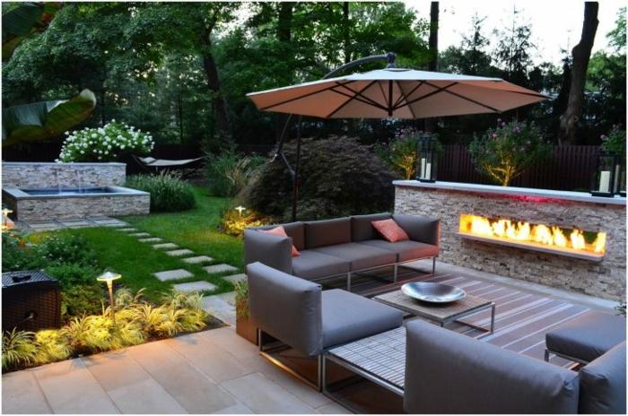 Sonnenschirm auf moderne Terrasse gestellt, ein eingebauter Kamin, Loungemöbel, kleiner Couchtisch