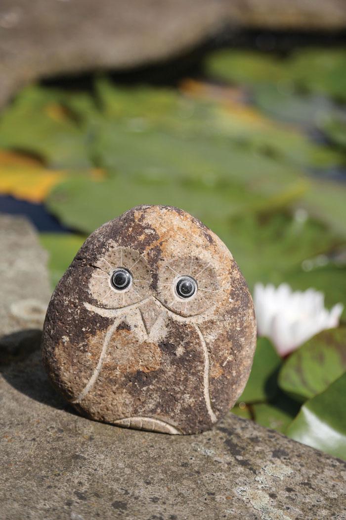 eine kleine eule aus einem stein, ein garten mit grünen pflanzen, eulen basteln vorlage