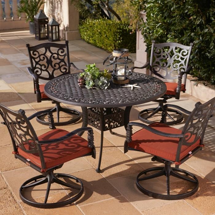 eine geräumige Terrasse dekorieren, ein eiserner Tisch und vier Stühle mit roten Kissen