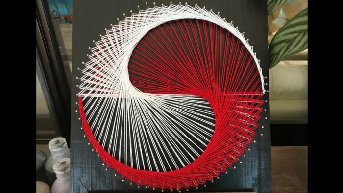 Fadenkunst - das Gute und das Böse sind zusammengeflochten in roter und weißer Farbe