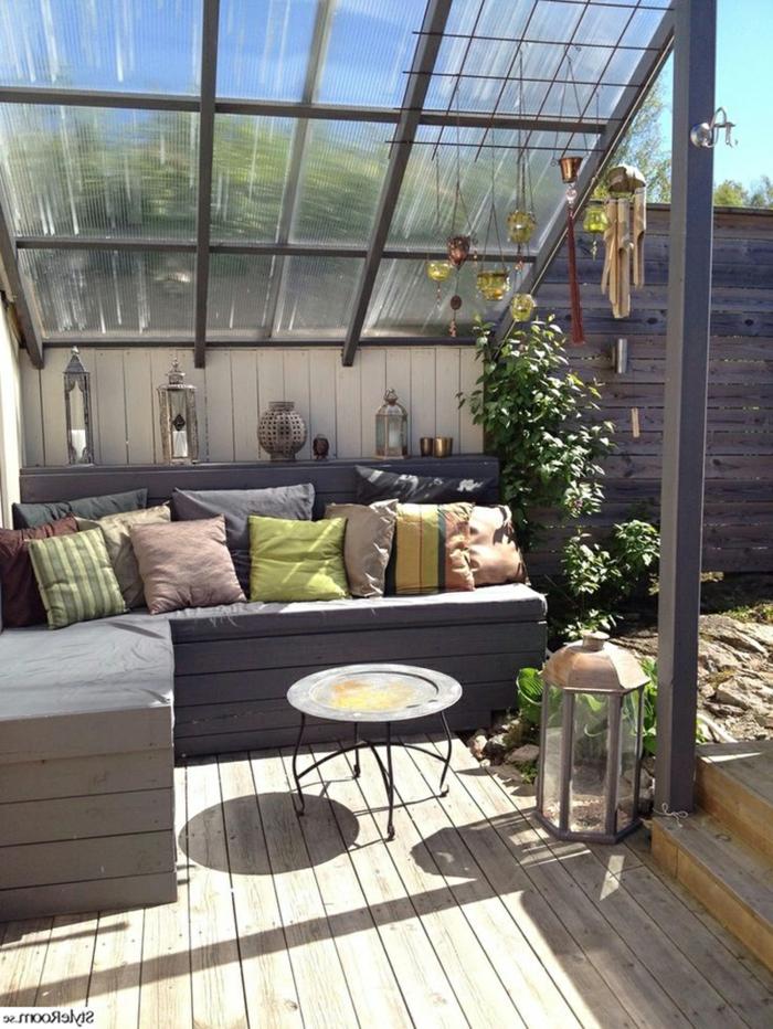 Terrasseüberdachung aus Glas, graues Ecksofa mit Kissen verziert, Terrasse dekorieren