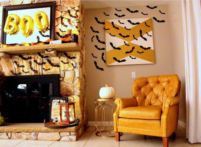 ein wohnzimmer mit einem großen gelben sessen, eine dekoration mit einem kleinen weißen kürbis, ein wand mit vielen kleinen schwarzen fledermäusen aus papier und mit schwarzen flügeln und schwarzen ohren, eine fledermaus malen