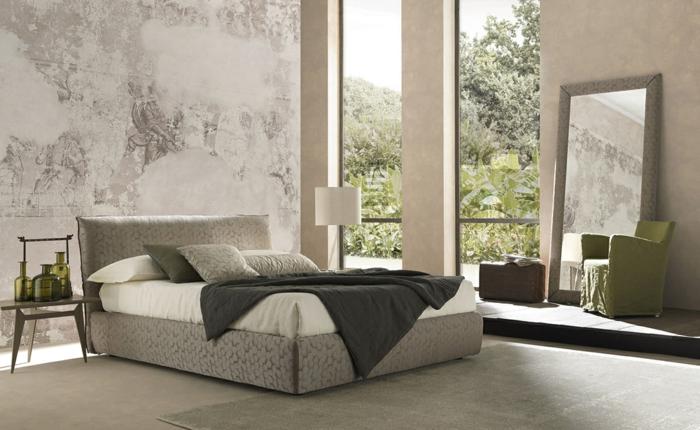 zwei großen Fenster, mit enormem Spiegel das Schlafzimmer dekorieren, ein graues Bett und ein graues Wand mit Ornamenten
