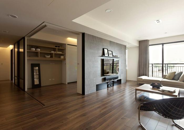 eine Einzimmerwohnung mit Trennwand für Zimmer, das auch Fernsehwand ist