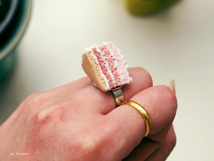 eine hand mit einem goldenen ring mit einer kleinen selbstgebastelten pinken torte aus einer fimo knete