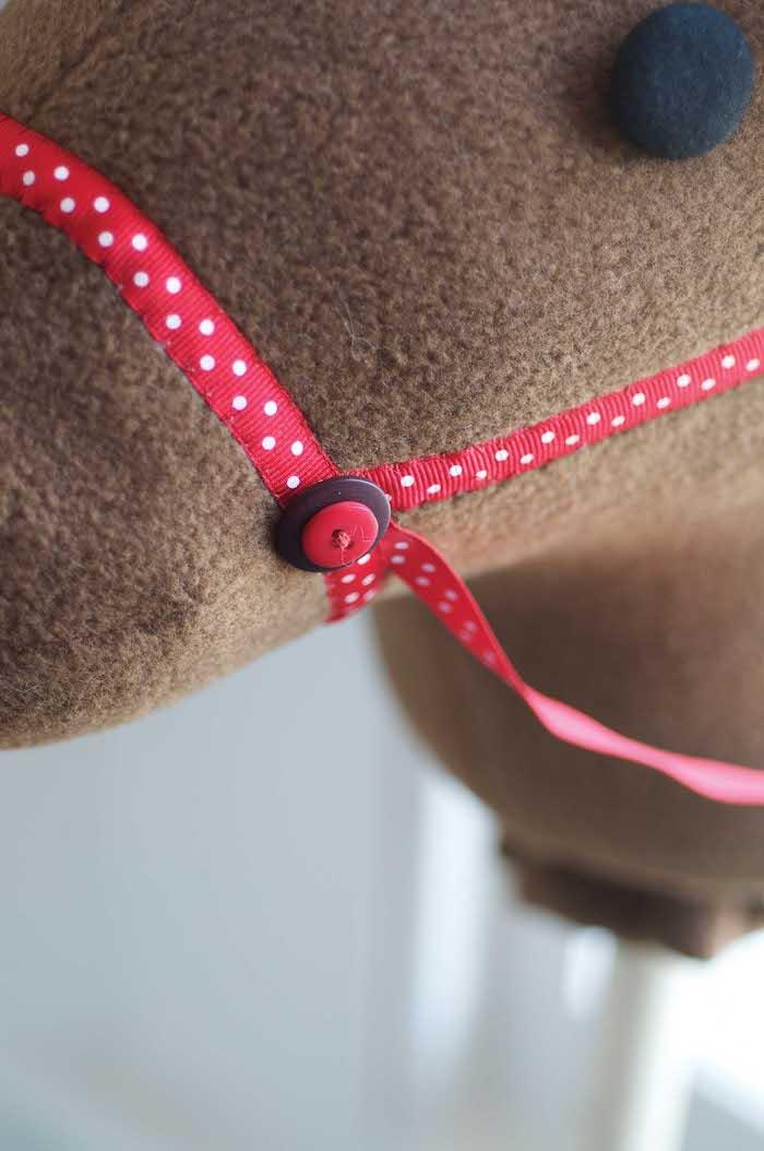 ein brauner hirsch mit einem roten knopf - ein braunes steckenpferd selber basteln, spielzeug für draußen