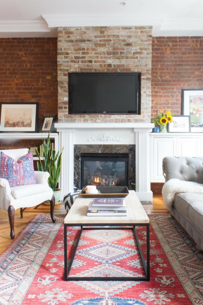 Wohnzimmer Fernsehwand, Backstein Optik, ein Kamin, ein Perserteppich, weißer Couchtisch