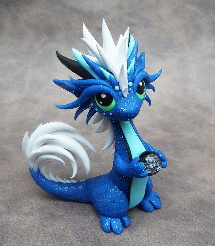 ein kleiner blauer drache aus einer blauen fimo knete, fimo drache mit schwarzen augen und einem weißen schwanz und einem kleinen ball, kleine fimo figuren