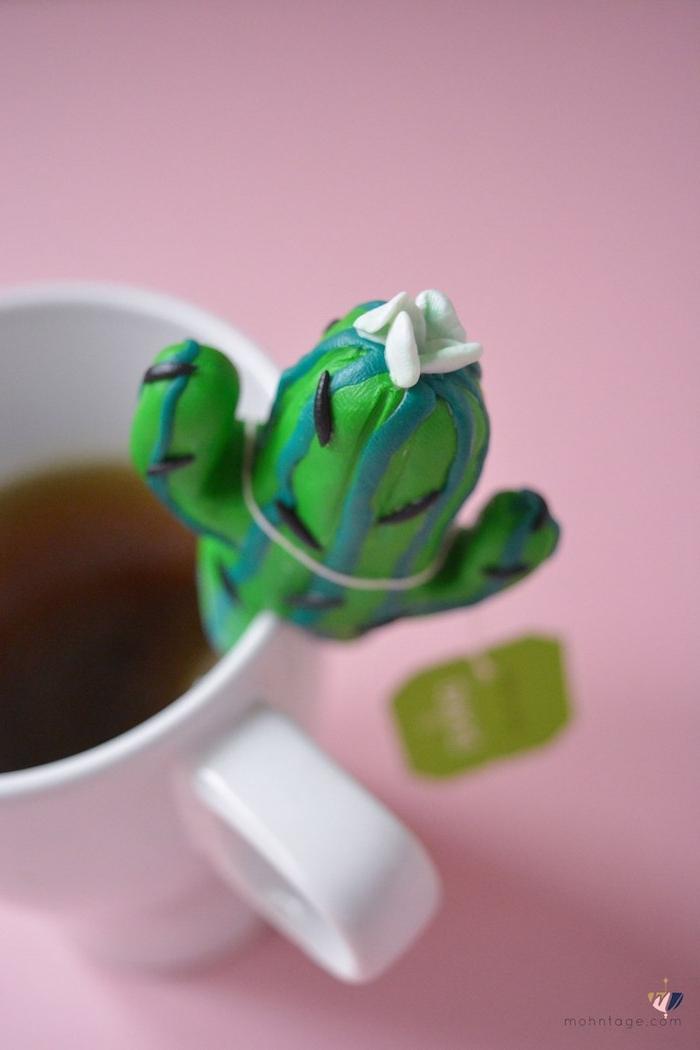 eine weiße tasse mit tee und einem kleinen grünen kaktus aus einer grünen fimo knete