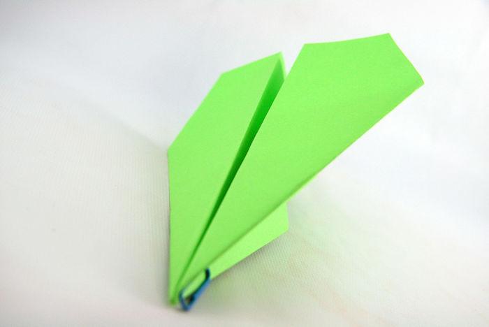 weißer tisch und ein kleiner grüner papierflieger, bastelideen mit papier, bester papierflieger der welt