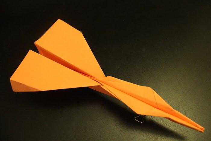 ein schwarzer tisch und ein kleiner oranger papierflieger, einen papierflieger falten