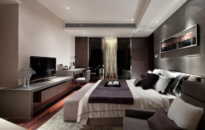 modern Schlafzimmer dekorieren, ein großes Doppelbett, ein grauer Sessel, ein Fernseher